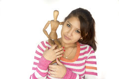 Cute Bolivian girl with wooden mannequin Royalty Free Stock Photo