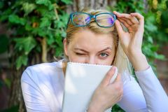 Cute bookworm in eyeglasses enjoy every chapter. Bookworm student relaxing with book green nature background. Woman. Blonde take break relaxing in park reading stock images