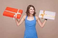 Cute boss demonstrate her gift boxes and smiling at camera. Studio shot Royalty Free Stock Images