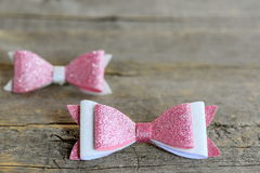Cute bows for hair. Pink and white shiny felt bows clips for little girls. Nice hair accessories on a wooden background Royalty Free Stock Photos
