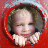 Cute boy. Peeking through the hole of playground equipment Stock Photography