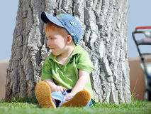 Cute Boy. A young boy resting against a huge tree Royalty Free Stock Photos