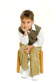 Cute Boy. A cute young boy sitting on a small wooden chair, isolated on white studio background Royalty Free Stock Photos