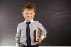 Cute boy against blackboard Royalty Free Stock Photos