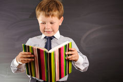 Cute boy against blackboard Stock Photography