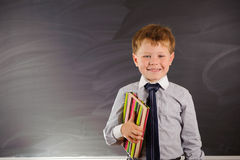 Cute boy against blackboard Stock Photos