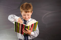 Cute boy against blackboard Stock Image