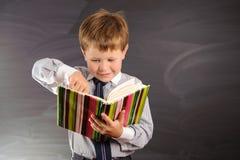 Cute boy against blackboard Stock Image