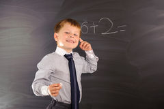 Cute boy against blackboard Stock Photo
