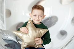 Free Cute Boy Aged 6-7 Years Old Sits In A Round Transparent Chair With A Star-shaped Pillow Smiling At The Camera. Royalty Free Stock Photos - 138536188