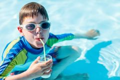 All inclusive vacation. Cute boy at all inclusive resort swimming pool sipping cocktail Stock Photos