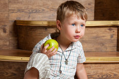A cute boy with an apple. A cute boy with an apple in his hand sitting on the steps Royalty Free Stock Photo