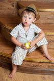A cute boy with an apple. A cute boy with an apple in his hand sitting on the steps Royalty Free Stock Photography