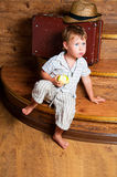 A cute boy with an apple. A cute boy with an apple in his hand sitting on the steps Stock Photography