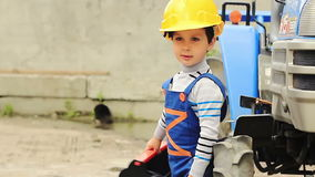 Cute boy as a worker stands near a tractor Stock Photography