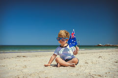 Cute boy with Australian flag on Australia day. Cute cheaky boy with flag of Australia sitting on the sand at the beach celebrating Australia Day royalty free stock photography