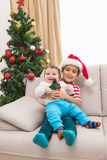 Cute boy and baby brother on couch at christmas Stock Photography