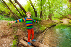 Cute boy balancing on a log bridge over the river Royalty Free Stock Photography