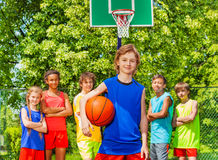 Cute boy with ball and happy friends behind. Cute boy with ball and international friends standing behind at basketball game outside during sunny summer day Stock Photos