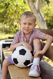 Cute boy with ball sitting on the bench Stock Photo