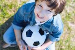 Cute boy with ball smiling after playing soccer. Future professional football player. Selective focus on a face of an adorable preteen kid looking into the Stock Images