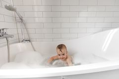 Cute boy in bathroom. Adorable little wet boy standing and smiling in white bath stock image