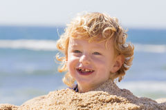 Cute boy at the beach. Adorable young blonde boy at the beach playing with the sand Stock Image
