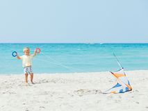 Cute boy on beach playing with a colorful kite Stock Images