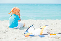 Cute boy on beach playing with a colorful kite Stock Image