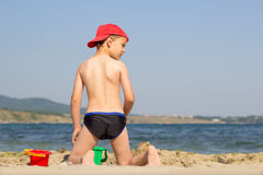 Cute boy on the beach staring with his back. Cute boy on the beach playing and staring at something with his back to camera Stock Photos