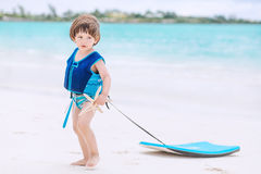 Cute boy on the beach. Cute boy with swimwear and life vest walking on the tropical beach with boogie board Stock Images