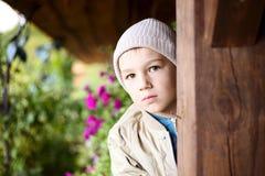 Cute boy behind a pillar stock images