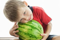 A cute boy and a big green watermelon. The child smiles and rejoices royalty free stock photo