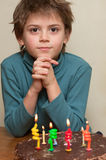 Cute boy at birthday cake. 8-year old boy at birthday cake with candles Stock Images