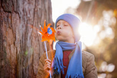 Cute boy blowing pinwheel Stock Photos