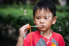 Cute boy blowing soap bubble. Portrait of handsome asian child blowing soap bubbles in garden with green blured nature background. Outdoor children funny Stock Photos