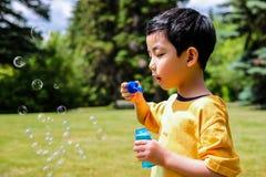 Cute Boy Blowing Soap Bubbles stock photo