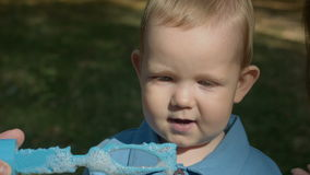 Cute boy blowing soap bubbles stock video footage