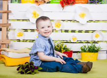 Cute boy in a blue denim shirt and tie, jeans and boots. Sitting on a bright spring and summer decorations and smiling Royalty Free Stock Image