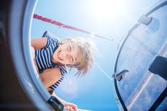 Little boy on board of sailing yacht on summer cruise. Travel adventure, yachting with child on family vacation. stock photography