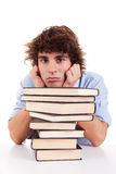 Cute boy bored, among books, on his desk Royalty Free Stock Images