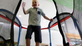 Little boy happily bounce on a trampoline in the playground. Toddler fails near the end. stock video footage