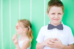 Cute boy with bow tie party accessory. Portrait of cute boy over colorful background holding bow tie party accessory Stock Photography