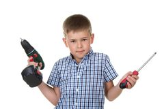 A cute boy builder in checkered shirt demonstrates the difficulty of choosing a tool, isolated on white background Royalty Free Stock Photography