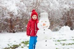 Cute boy, building a snowman in a garden, having fun Royalty Free Stock Image