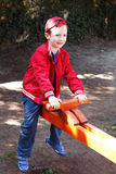 Cute boy in cap on seesaw Stock Photos