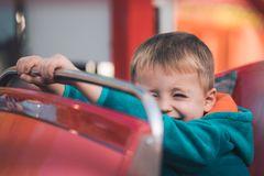 Cute boy in a carousel car royalty free stock image