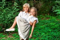 Cute boy carrying girl in arms. Portrait of cute boy carrying girlfriend in arms outdoors Stock Photography