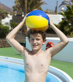 Cute boy carrying a plastic ball on stock photos