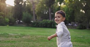 Cute boy in a casual stylish suit running through the park very energetic smiling large looking to the camera his stock video